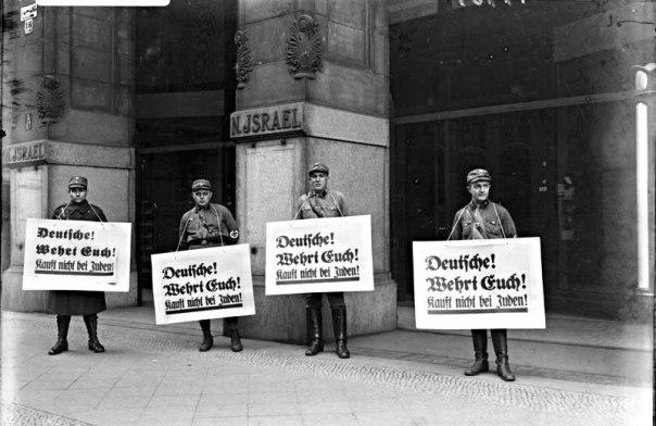 """חיילים נאצים נושאים שלטים שבהם נכתב: """"גרמנים! הגנו על עצמכם! אל תקנו מיהודים!"""", 1933"""