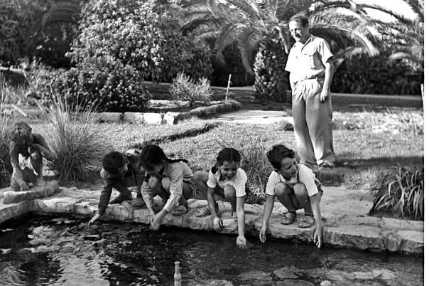 """את הזמר שרה מזמזמת קבוצת ילדים קטנה, יחפת רגליים. קיבוץ משמר העמק, 1948  צילום: לע""""מ"""