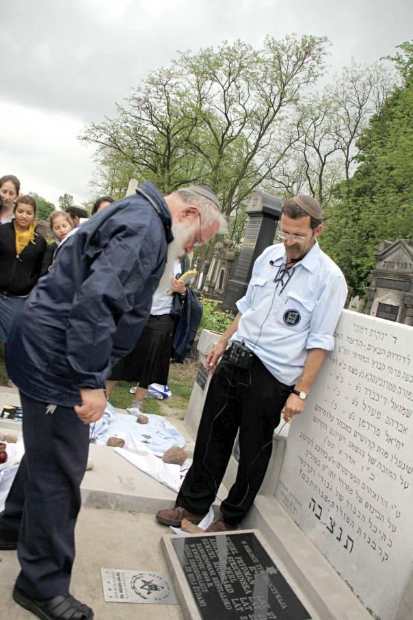"""הרב חיים דרוקמן ודני הירשברג קובעים את סמל התנועה על קבר ארבעת חברי בני עקיבא בבית הקברות בלודז'  צילומים: יח""""צ בני עקיבא"""
