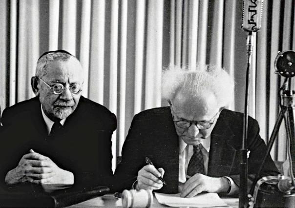 """""""להיות עם סגולה"""". בן גוריון חותם על מגילת העצמאות, משמאלו הרב פישמן־מימון  צילום: לע""""מ"""