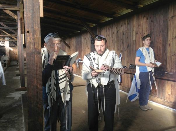 תפילה בצריף שבו שהה מנחם סנדובסקי בבירקנאו. במרכז: יקי מנדלסון, משמאלו מנחם סנדובסקי