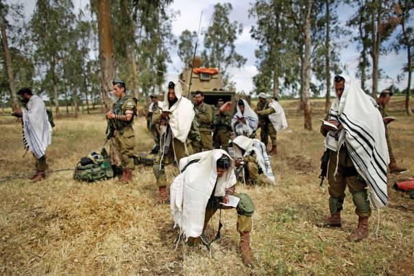 """גורם מאחד בבתי הכנסת ובשדה הקרב. תפילת חיילים במהלך """"צוק איתן"""", 2014  צילום: EPA"""