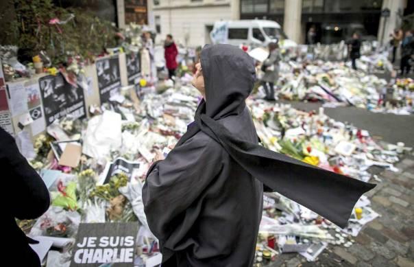 ביקורת עצמית לוקה בחסר. אישה מוסלמית באתר ההנצחה ליד משרדי שרלי הבדו בפריז צילום: אי.פי.אי