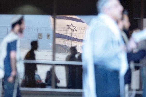רק מחויבות דתית לארץ ישראל כארץ הקודש יכולה לשקם את רעיון המרכז הרוחני. יהודים אמריקנים המבקרים בארץ בתפילה בשדה התעופה בן גוריון צילום: אי.פי.אי