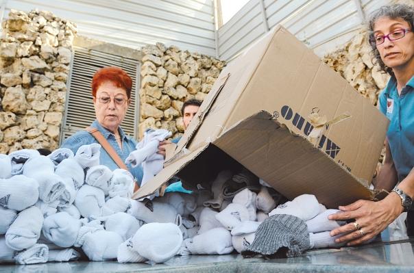 """געגועים לאחווה הלאומית שאחזה בעם כולו. מתנדבות בחלוקת חבילות לחיילים בימי """"צוק איתן"""" צילום: זואי וייר, פלאש 90"""
