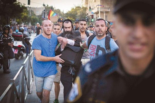 """הקהילה הלהט""""בית היא מראה דתית שלו. ישי שליסל לאחר הדקירות במצעד הגאווה, ירושלים 2015 צילום: פלאש  90"""