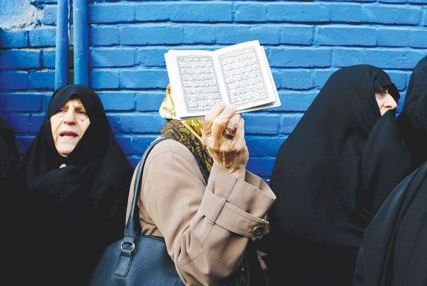"""""""לאיסלאם יש סיכוי גדול יותר לעבור רפורמה מאשר ליהדות האורתודוקסית"""" מפגינה שבידה ספר הקוראן, איראן 2015 צילום: אי.פי.אי"""