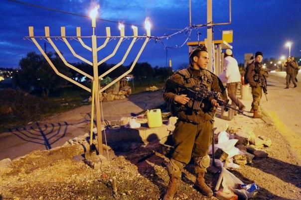 ראשית הנס מצויה בעצם המוכנות להעז להילחם. חיילים בשמירה ליד הכניסה לאלון שבות, חנוכה 2014 צילום: גרשון אלינסון, פלאש 90