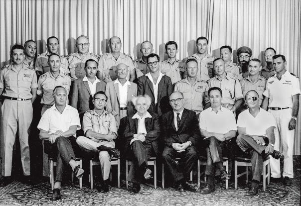 """חלש על המערכה המורכבת ביותר שהייתה לצה""""ל מעודו. גביש, בשורה העליונה משמאל, עם ראש הממשלה דוד בן גוריון וצמרת משרד הביטחון, 1961 צילום: משרד הביטחון, לע""""מ"""